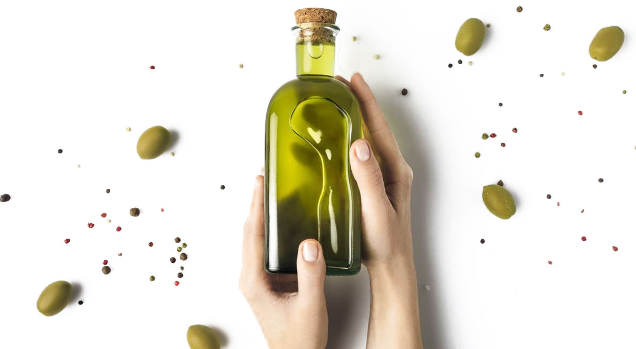 A bottle of olive oil held in hands