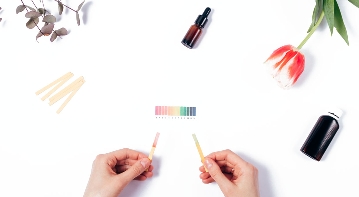 Person evaluating the pH of skin care products using litmus strips