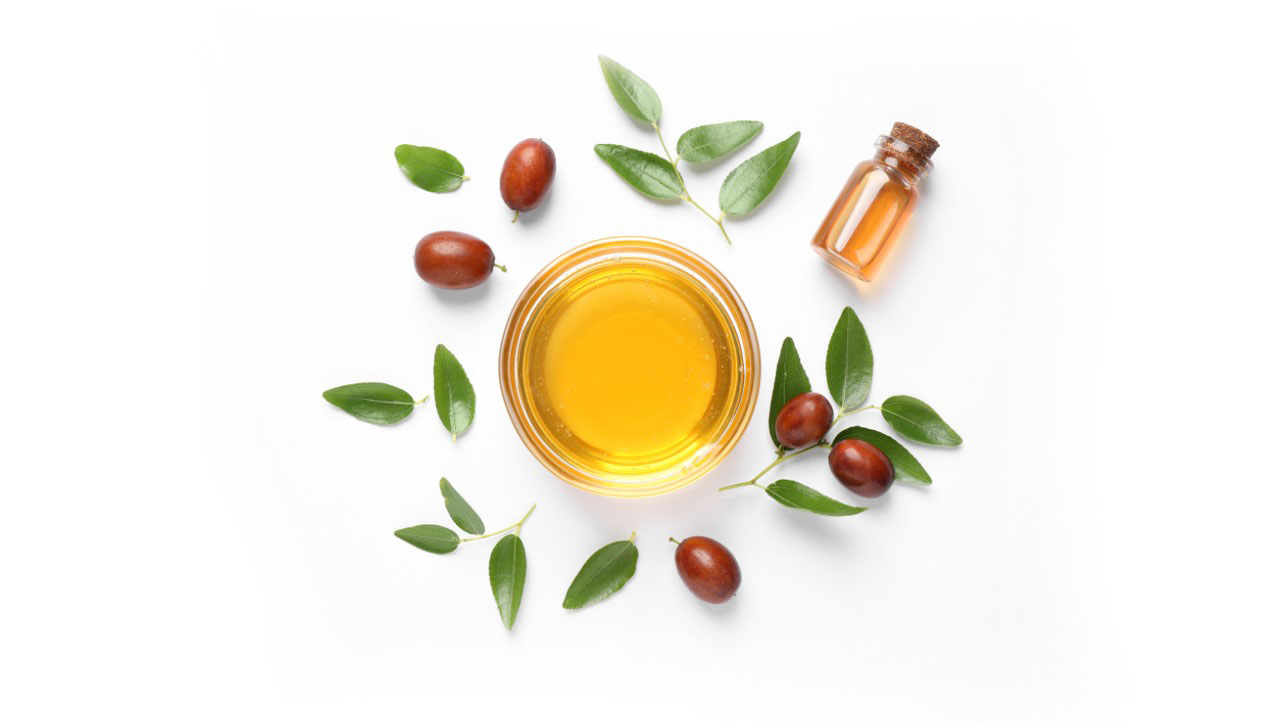 Small bowl of jojoba oil surrounded by several leaves and beans